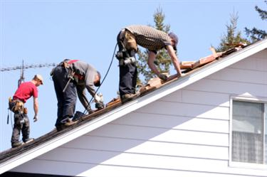 Roof Installation in Lexington KY. Three roofers laying new shingle on a roof in Lexington.